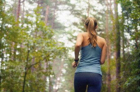 healthy lifestyle fitness sporty woman running early in the morning in forest area, fitness healthy lifestyle concept Imagens