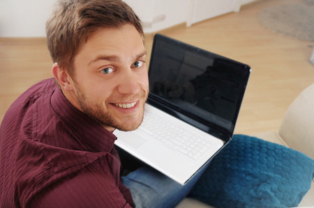 portrait of attractive young man with laptop on the sofa at home, credit business concept photo
