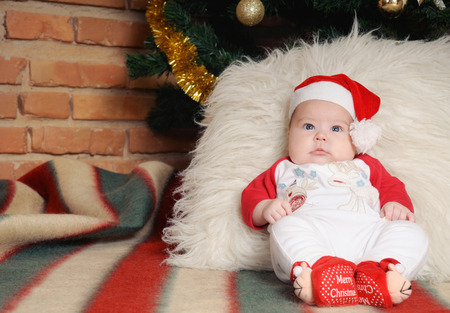 baby near christmas tree: cute newborn baby in Santa hat sitting near Christmas tree, holiday concept