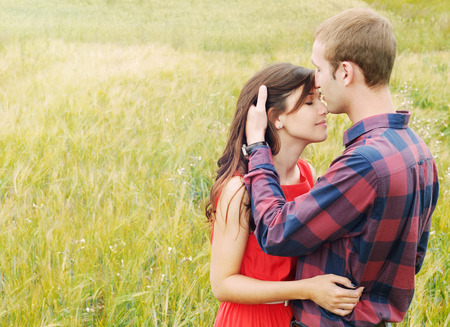 parejas sensuales: impresionante retrato al aire libre sensual de la joven y atractiva con estilo de moda pareja de enamorados bes�ndose en el campo de verano Foto de archivo