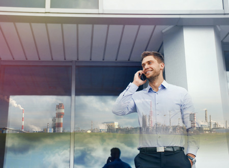 double exposure of businessman with phone device and industrial enterprise on urban building background photo