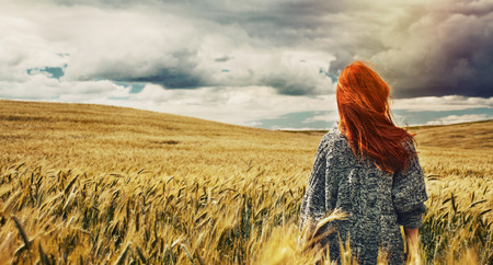 morning walk: fashion young red hair woman standing back outdoor on breathtaking view of dramatic storm sky in the field