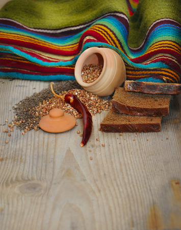 coverlet: Still life with bread, buckwheat and cumin on a wooden board Stock Photo