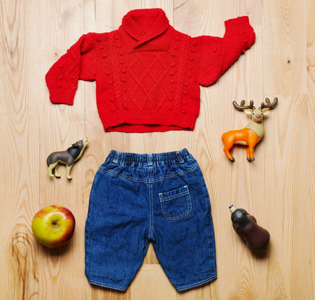 top view fashion trendy look of baby clothes and toy stuff on the wooden floor, baby fashion concept