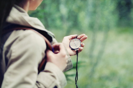 hiking trail: young woman discovering nature in the forest with compass in hand, travel lifestyle concept Stock Photo