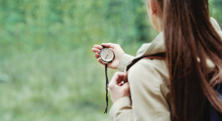 compass: young woman discovering nature in the forest environment with compass, travel lifestyle concept