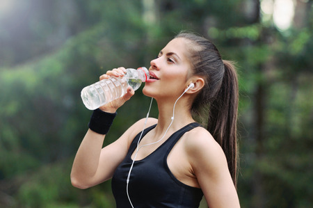 hacer footing: el estilo de vida de buena condición física mujer deportiva corriendo temprano en la mañana en la zona de bosque, estilo de vida saludable concepto