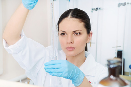 chemical laboratory scene: attractive young student scientist observing liquid measures medicine concept