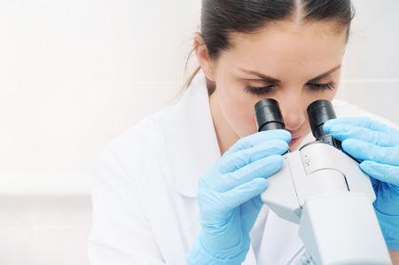 biotecnologia: investigador médico joven mirando a través de microscopio en la medicina concepto de laboratorio