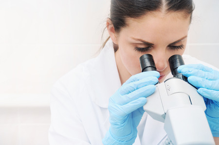 researching: young woman medical researcher looking through microscope in laboratory medicine concept