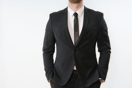 흰색 배경에 주머니에 손 검은 양복 비즈니스 사람 몸의 일부를 닫습니다; 비즈니스 개념