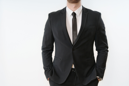close up part of business man body in black suit with hands in pockets on white background; business concept Foto de archivo