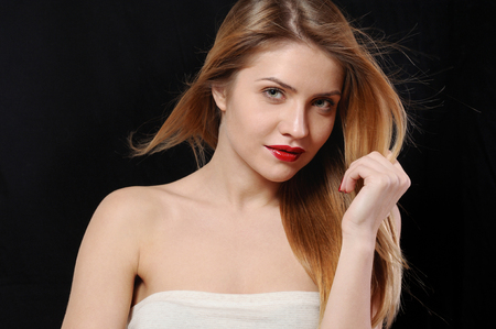 sensitive skin: fashion portrait of beautiful young blonde woman with perfect makeup and sensitive skin on black background Stock Photo