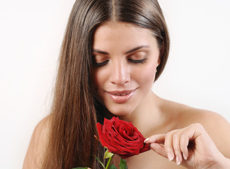 beautiful rose: Cute beautiful woman tears off petals of red rose on white background. Pure skin and strong healthy bright hair. Spa beauty concept