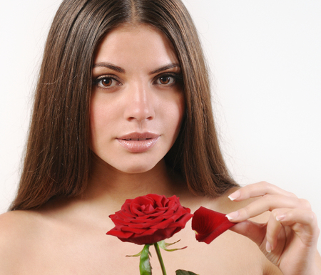 beautiful rose: Cute beautiful woman tears off petals of red rose and looking at camera. White background. Pure skin and strong healthy bright hair. Spa beauty concept