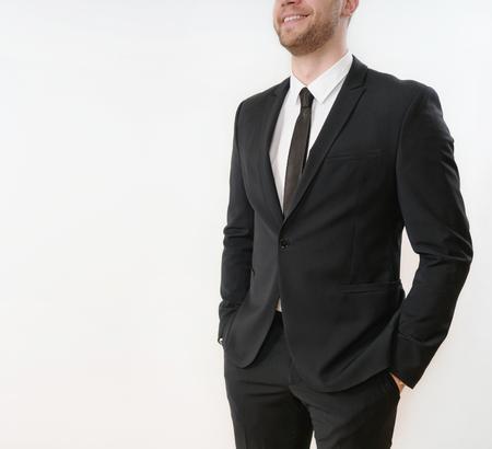 vicino parte di sorridente uomo d'affari in abito nero con le mani in tasca su sfondo bianco; concetto di business