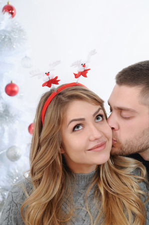christmas spirit: Fairy kiss near Christmas tree. Christmas spirit concept. Stock Photo