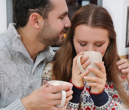 nook: Young couple drinking chocolate with marshmallow on a background of fireplace. cosy nook
