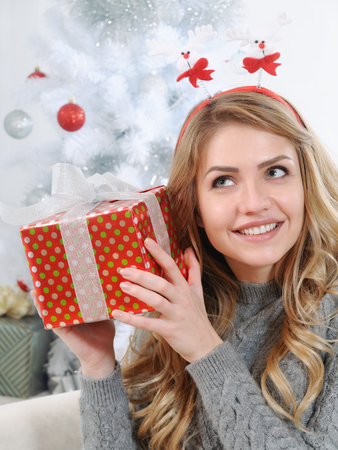 figure out: an attractive young woman trying to figure out the gift she received on Christmas morning, happy holiday concept Stock Photo