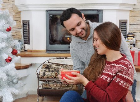 young adult man: The young adult man make Christmas present his girlfriend. Christmas and New Year concept Stock Photo