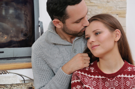 nook: young happy couple on the background of fireplace. cosy nook