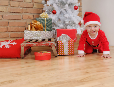santa suit: cute happy little baby boy in Santa suit and old vintage sled with gifts near Christmas tree. Stock Photo