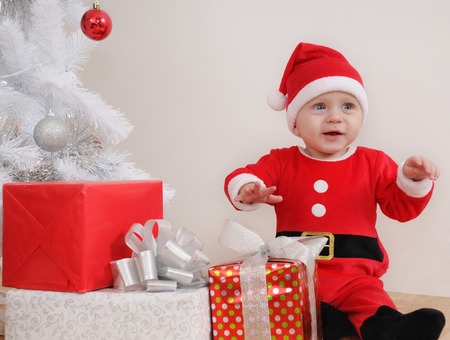 santa suit: cute happy little baby boy in Santa suit with gifts near Christmas tree.