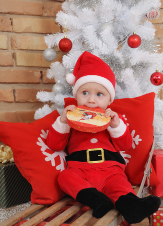 baby near christmas tree: cute happy little baby boy in Santa suit on old vintage sled with gifts near Christmas tree. Stock Photo