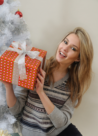 figure out: an attractive young woman trying to figure out the gift she received on Christmas morning.