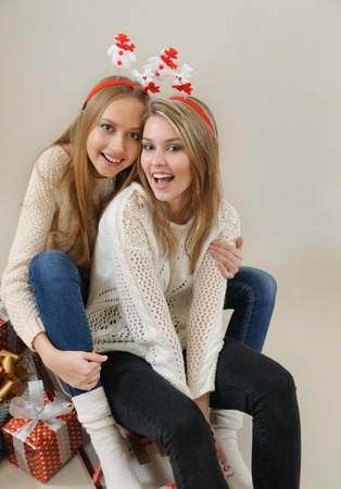 christmas spirit: Two funny girls on the sled with gifts. Christmas and New Year concept. Studio shot on grey background. Christmas spirit