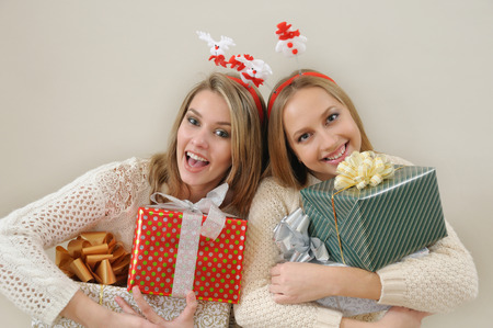 christmas fun: Two happy women with gift boxes looking at camera. Stock Photo
