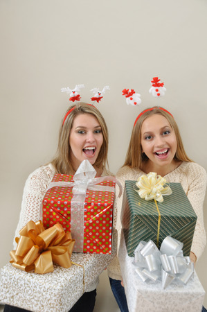 christmas spirit: Two smiling young women offer gifts. Christmas and New Year concept. Studio shot on grey background. Christmas spirit