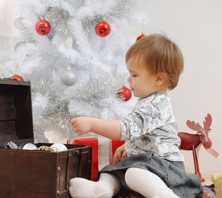 christmas spirit: cute little baby girl playing with Christmas toys. happy holiday concept. happy family. Christmas spirit