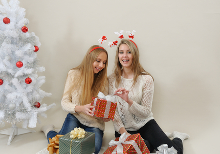 young tree: Two happy women with gift boxes open one of them. Stock Photo