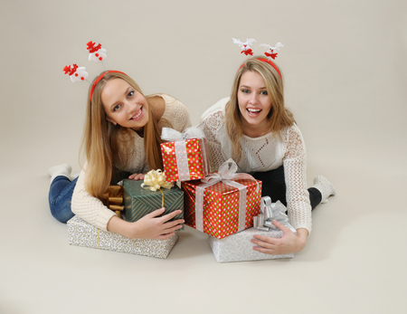 Two happy women hug heap of gift boxes. Stock Photo