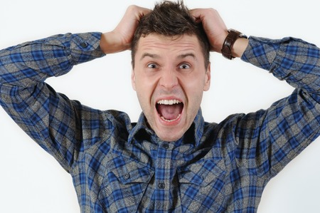 bawl: emotional portrait of young angry screaming man pulling his hair. Human emotion facial expression feeling