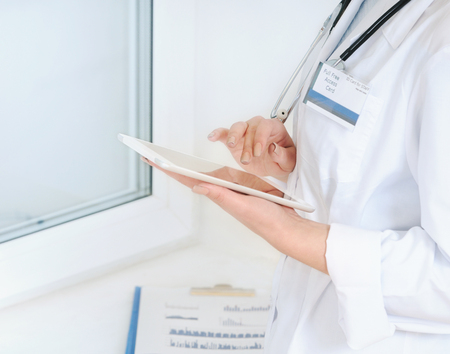helthcare: Close up view of woman doctor at hospital, writing on tablet computer. Helthcare concept