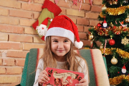 very cute baby girl with little red box in hands on the chair near Christmas tree, happy holiday concept, happy family