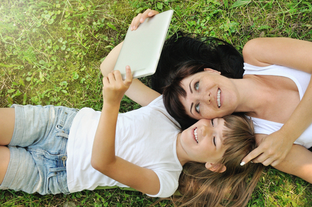 lifestyle family portrait of happy girl and her mother having fun on the grass in sunny summer day, happy lifestyle family concept, lifestyle concept Stock Photo