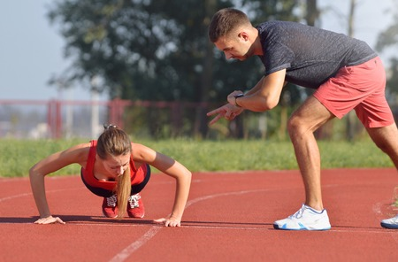 outdoor outside: Fitness woman doing push-ups during outdoor cross training workout. Beautiful young and fit fitness sport model training outside insummer. Personal trainer working with his client.