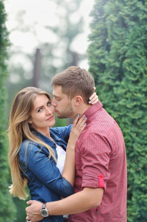Young beautiful girl staring at camera while being kissed by her boyfriend. Love, relationship, family and people concept - smiling couple hugging in park Foto de archivo