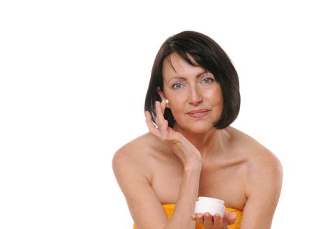 portrait of pretty senior woman using face cream