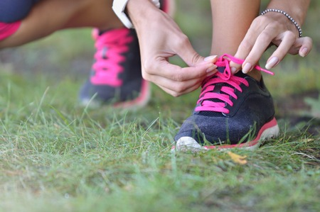lacing sneakers: Woman ties up shoelaces on sneakers