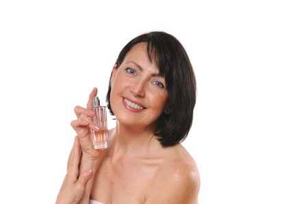 Mature well groomed woman with bottle of perfumes