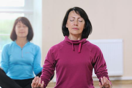 Two mature women sit on the lotus position