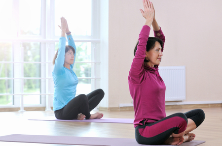 Active sportive mature women doing exercise in fitness studio. Beautiful mature women in sports clothes working out on yoga mat at gym