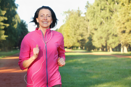 Portrait of elderly woman running with headphones in the park in early morning. Attractive looking mature woman keeping fit and healthy. Standard-Bild
