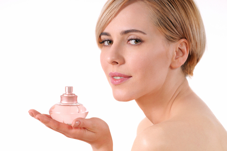 Close-up portrait of pretty woman holding on own palm the bottle of perfumes.