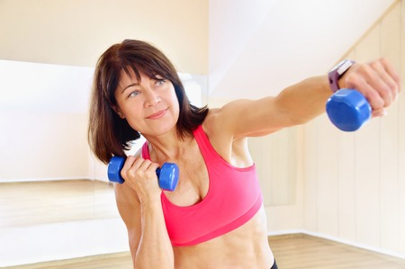 Fitness mature woman working out with dumbbells.