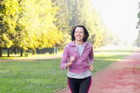 Portrait der älteren Frau laufend in den Park am frühen Morgen. Attraktive schauende reife Frau, die fit und gesund hält. Standard-Bild